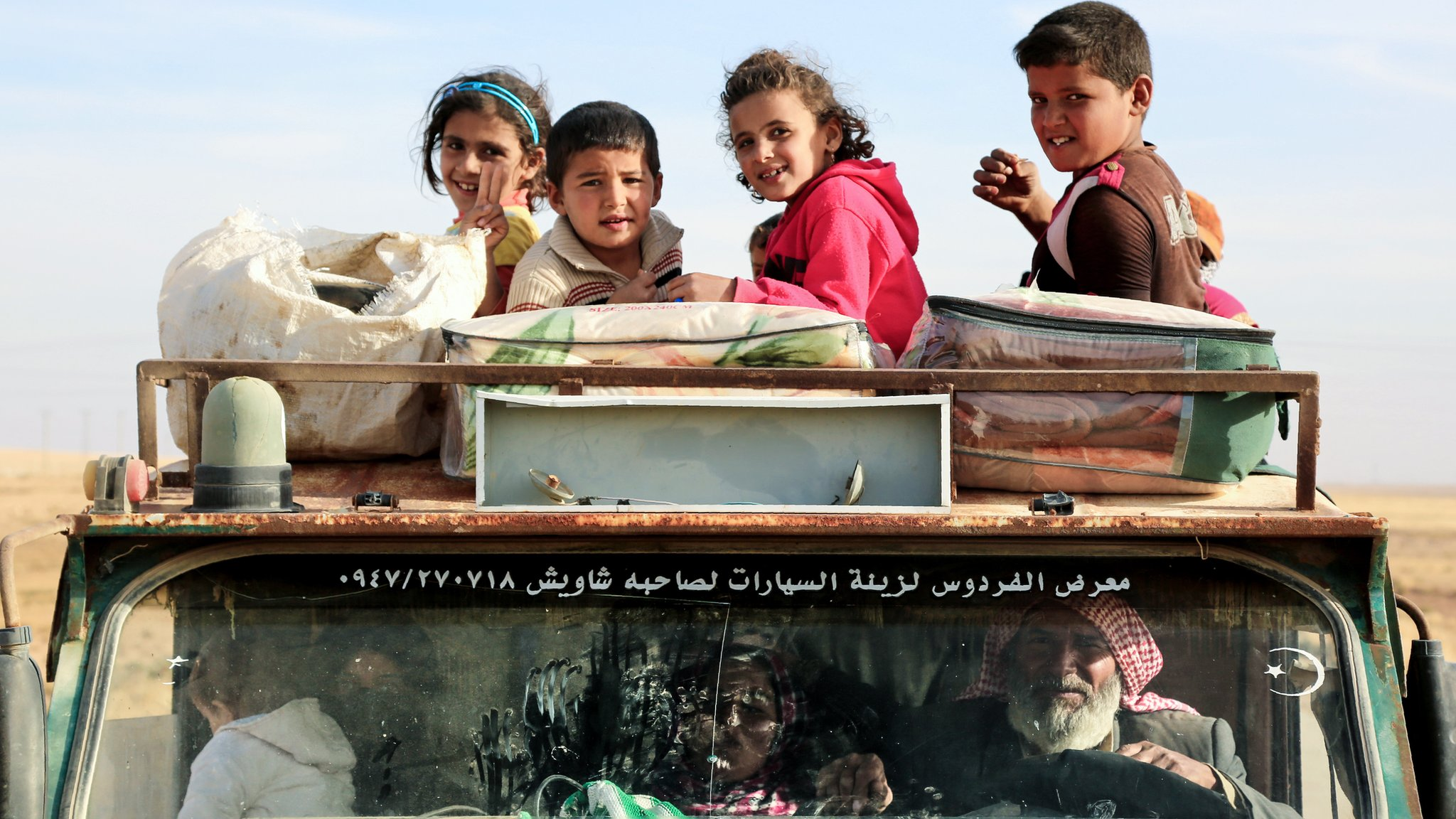 Children sit on top of a truck carrying Syrian refugees
