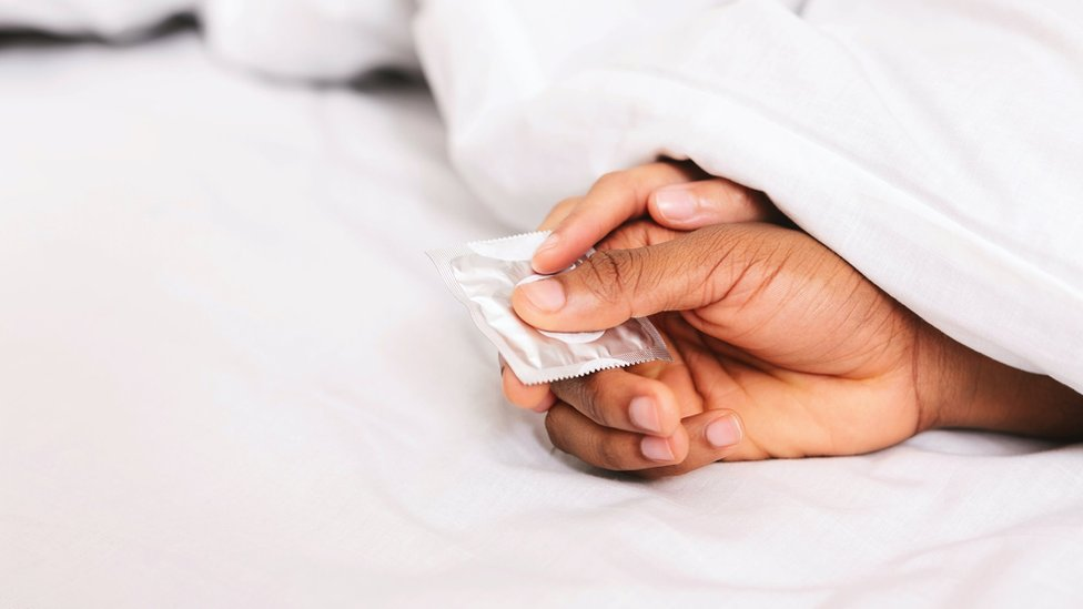 The hands of a young couple holding a condom (stock photo)