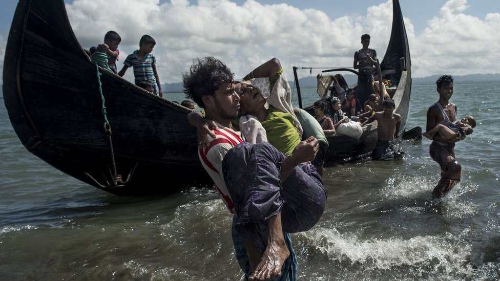 Bangladeshi man helps Rohingya Muslim refugees to disembark from a boat on the Bangladeshi shoreline of the Naf river after crossing the border from Myanmar in Teknaf on 30 September 2017