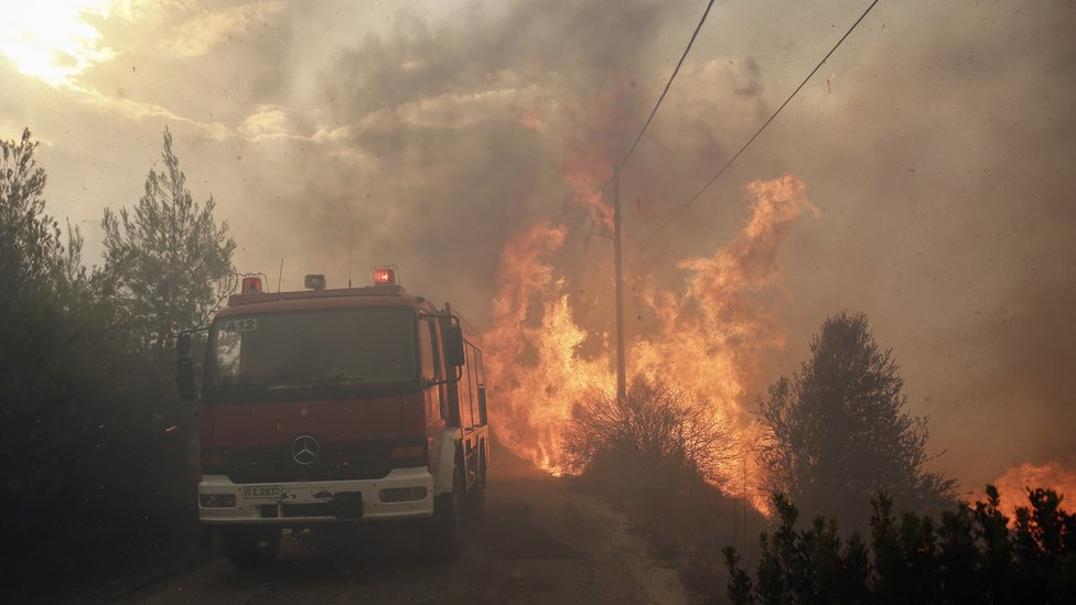 Flames are seen next to firefighting vehicle during a forest fire in Neo Voutsa, a northeast suburb of Athens, Greece, 23 July 2018