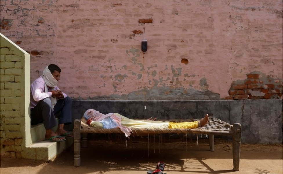 A man sits next to his wife, who is suffering from fever as she receives treatment at a clinic set up by a local villager, amidst the spread of the coronavirus disease (COVID-19), in Parsaul village in Greater Noida, in the northern state of Uttar Pradesh, India, May 22, 202