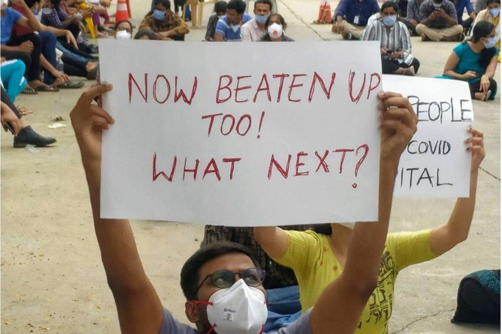 """O médico Vikas Reddy usa máscara e segura um cartaz com dizeres """"agora também fui espancado, o que vem depois?"""""""