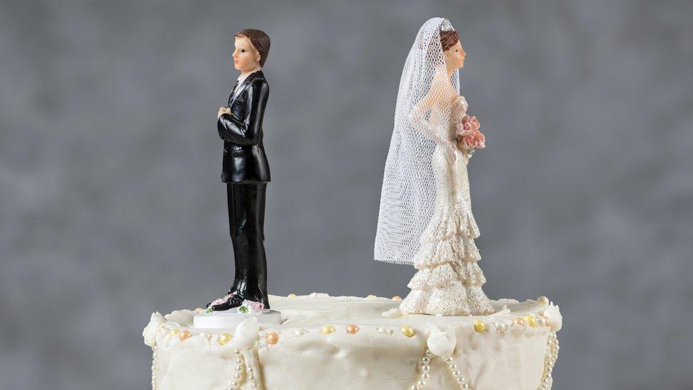 bride and groom on cake facing away