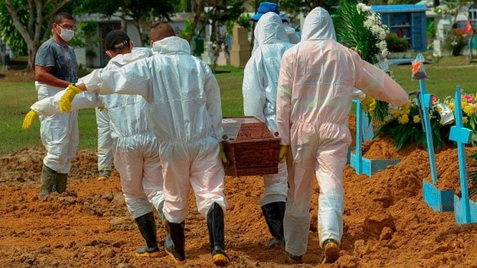 Trabalhadores carregam um caixão num cemitério