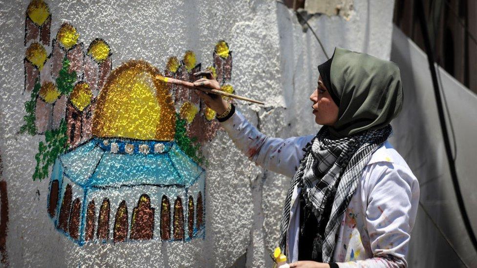 الفنانة الفلسطينية عطاف النجيلي ترسم قبة الصخرة على جدار مبنى مدمر في مدينة غزة، 24 مايو/أيار 2021