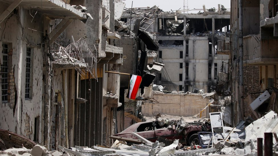 An Iraqi flag is seen amid destroyed buildings during fighting between Iraqi forces and Islamic State militants in the Old City of Mosul (4 July 2017)