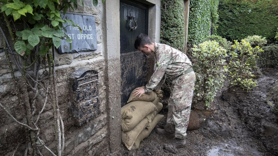 Soldier stacking sandbags in front of the old post office front door
