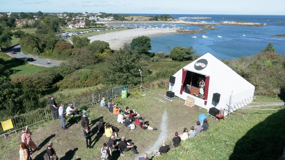 Small tent with small audience by the sea