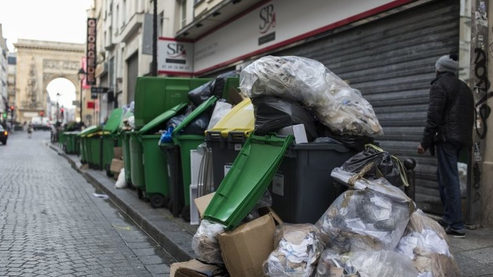 A man walks past a pile of rubbish bags in Paris (08 June 2016)