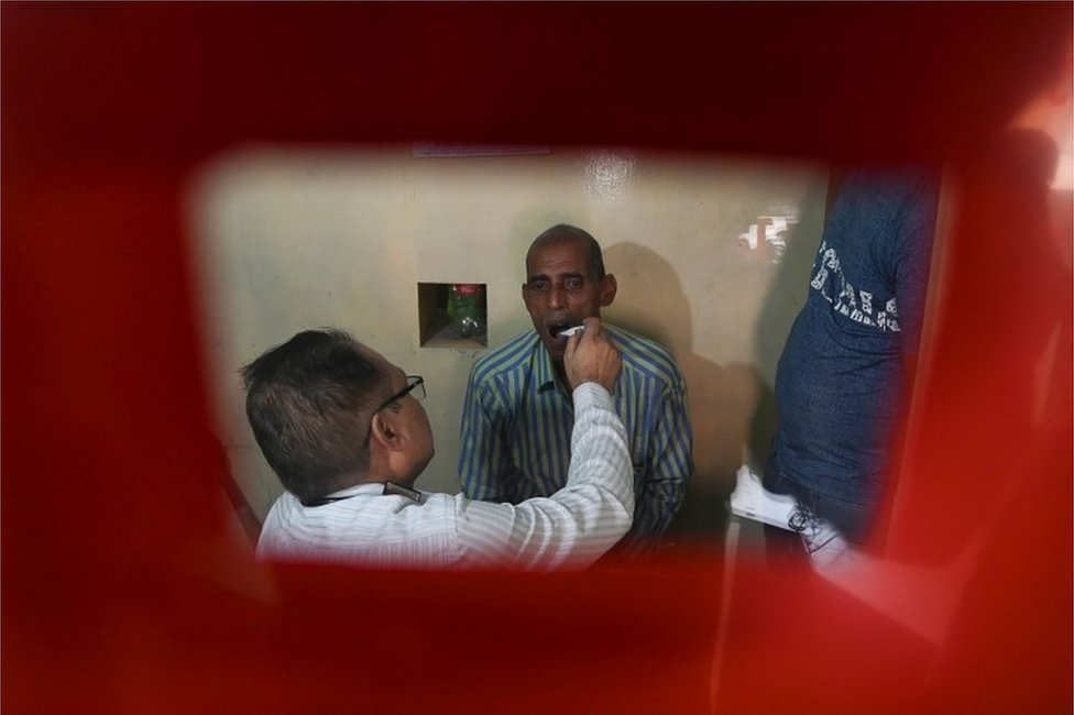 In this photograph taken on September 26, 2019, a doctor checks a suspected tuberculosis (TB) patient at a DOTS (directly observed treatment, short-course) Centre in New Delhi