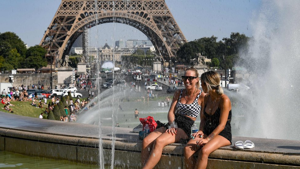 Women cool off at the Trocadero Fountains next to the Eiffel Tower in Paris
