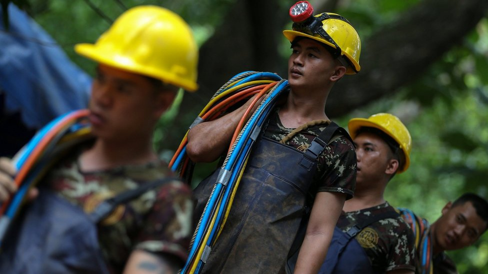 Rescuers carry cables outside the Tham Luang cave complex in Thailand on 5 July 2018