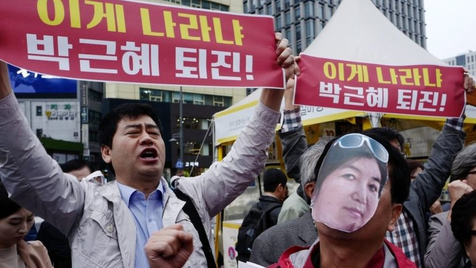 "A protester (right) wears a cut-out photograph of Choi Soon-sil, while another demonstrator holds a banner reading: ""President Park Geun-hye's resignation"" in Seoul on 27 October 2016"