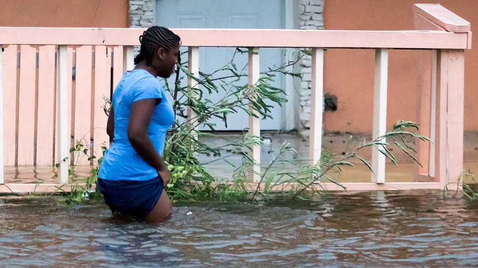 A woman walks in a flooded street after the effects of Hurricane Dorian arrived in Nassau, Bahamas, September 2, 2019