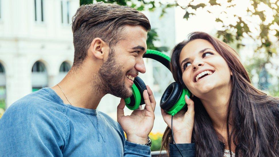 Dos jóvenes escuchando música con los mismo auriculares.