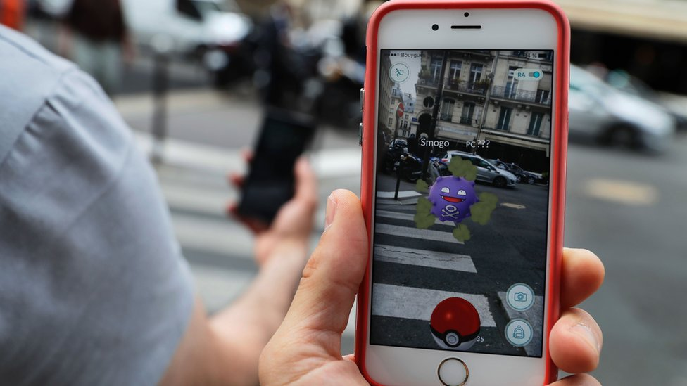 """This picture taken on July 26, 2016 near the Louvre museum's pyramide in Paris shows the """"Pokemon Go"""" app on the screen of a smartphone"""