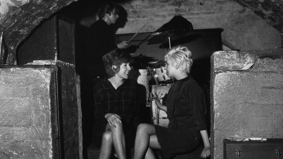 24th April 1963: Pop singer Cilla Black (left) talking to a friend at the Liverpool music venue The Cavern