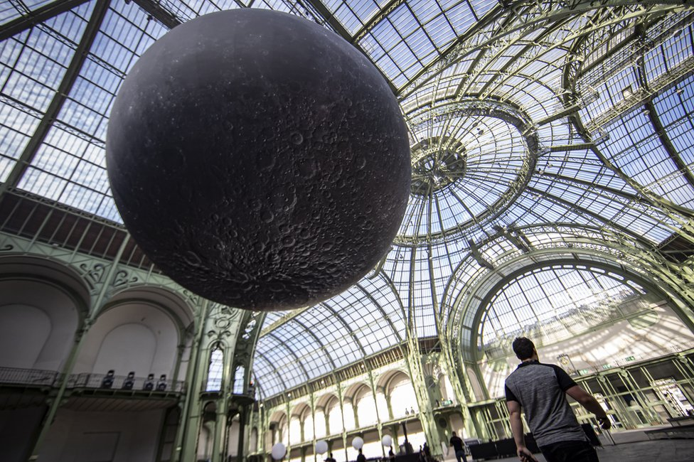 """A replica of the moon hangs from the glass ceiling of the Grand Palais ahead of the """"Mooon Party"""" celebrating the 50th anniversary of the moon landing, in Paris, France"""