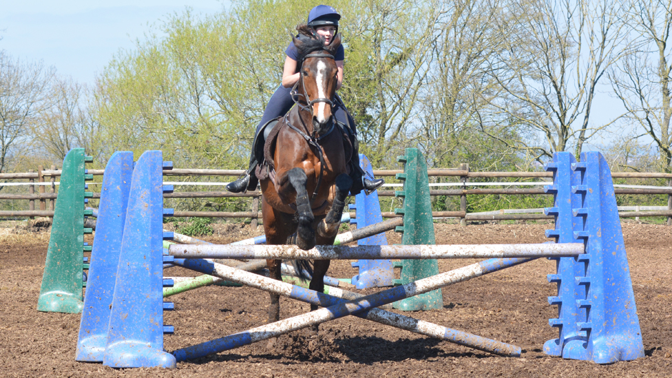Matilda riding a horse as it goes over some jumps