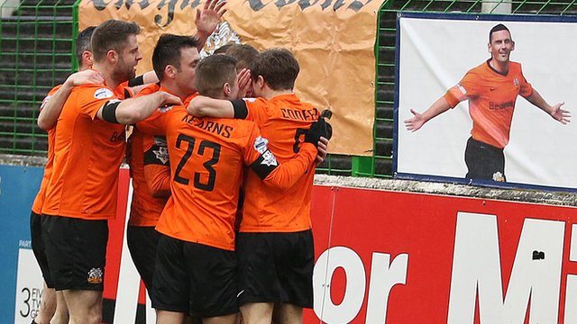 Glenavon players celebrate the opening goal against Glentoran in front of a picture of former player Mark Farren who passed away this week