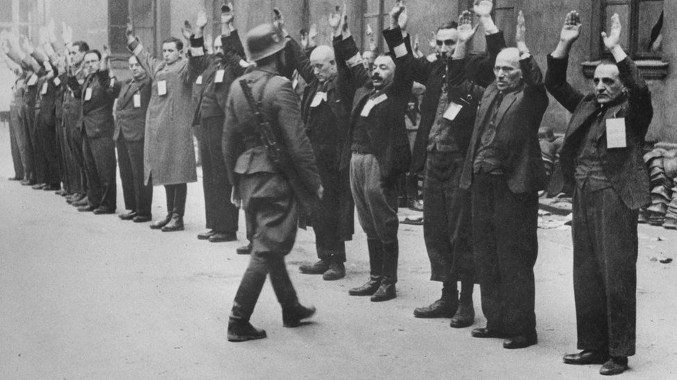 A Nazi SS solider inspects Jewish workers in the Warsaw Ghetto, 1943