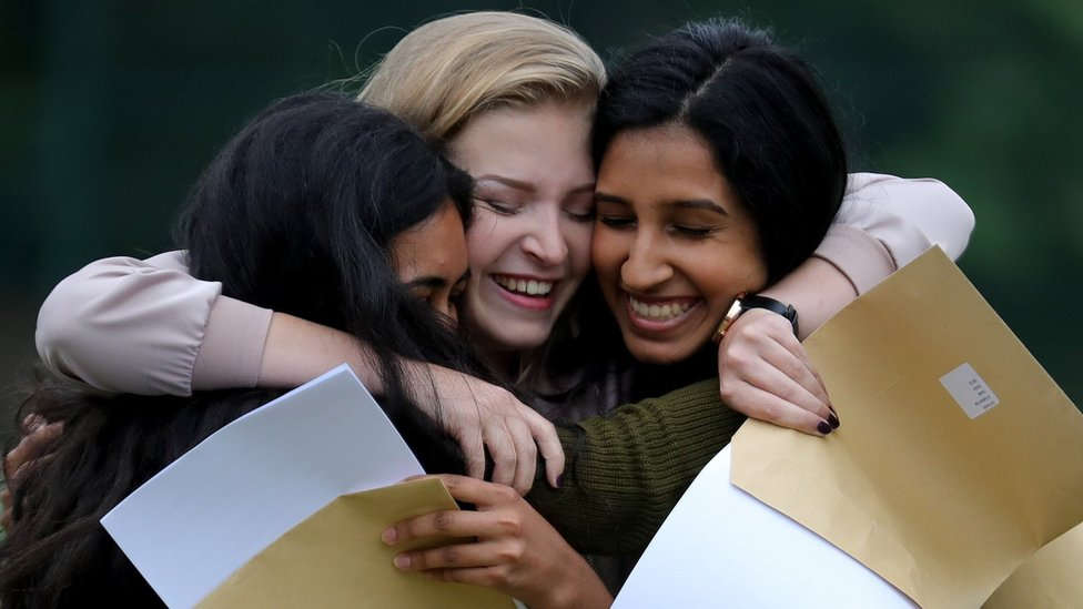 Three teenage girls hugging after getting their A level exam results
