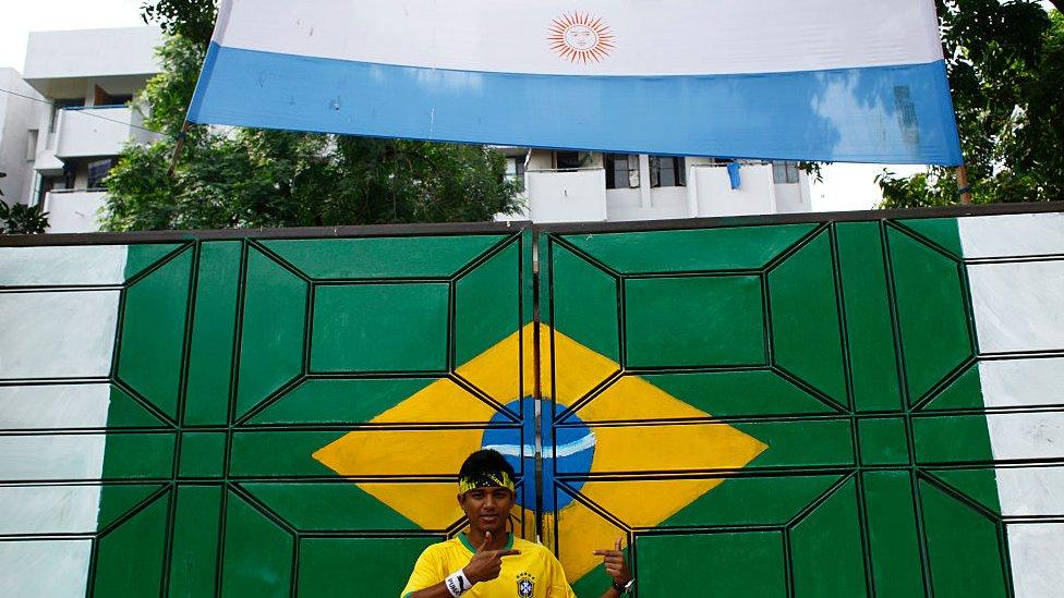 Persona fotografiándose con las banderas de Brasil y Argentina en Bangladesh.