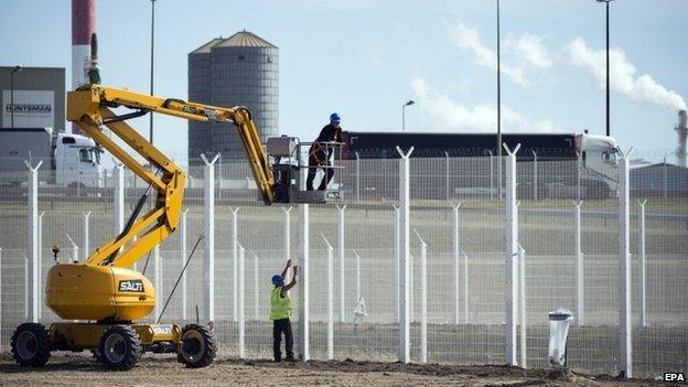 Workmen building a high fence near Calais port