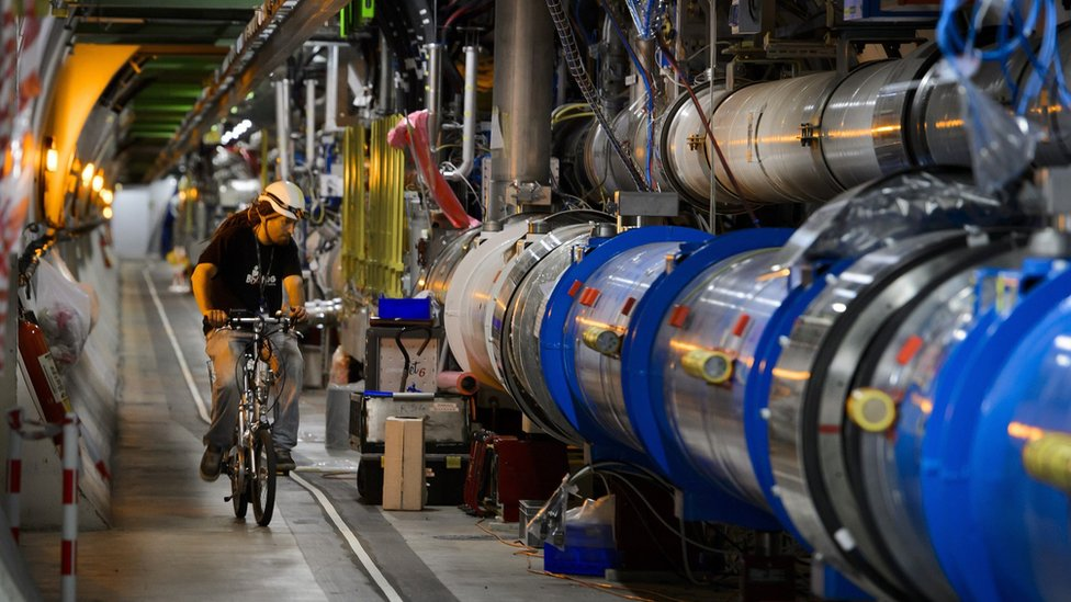 A worker rides his bicycle in a tunnel of the European Organisation for Nuclear Research (CERN) Large Hadron Collider (LHC), during maintenance works on July 19, 2013