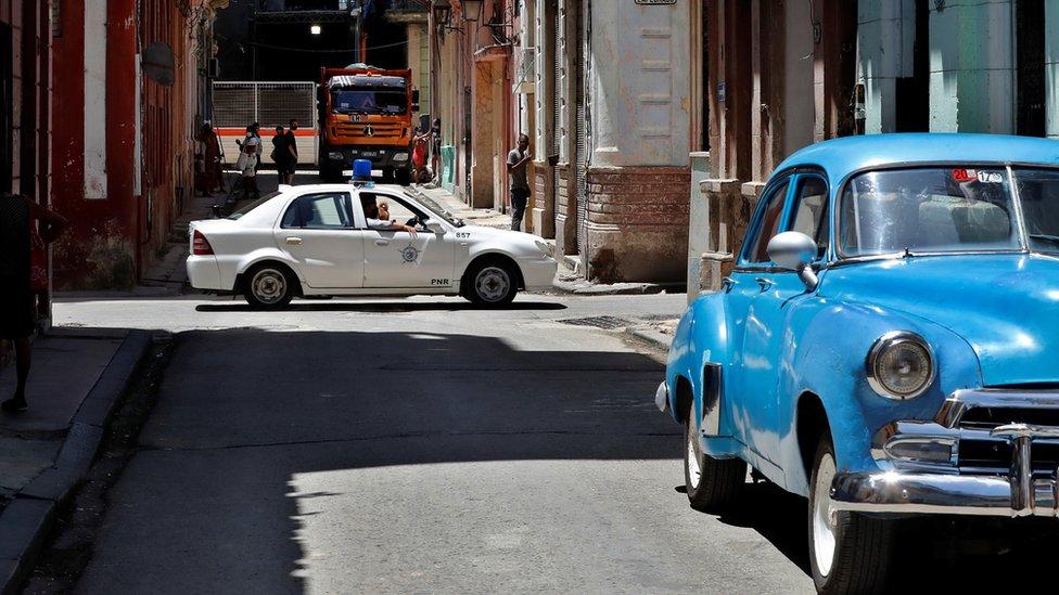 Um carro de polícia e um carro popular azul em uma rua de Havana