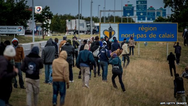 Migrants walk in the direction of the Eurotunnel in Coquelles near Calais, northern France, on late July 29, 2015