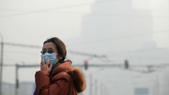 Woman standing in smog in Beijing