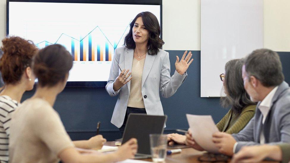 Una mujer hace una presentación en una oficina