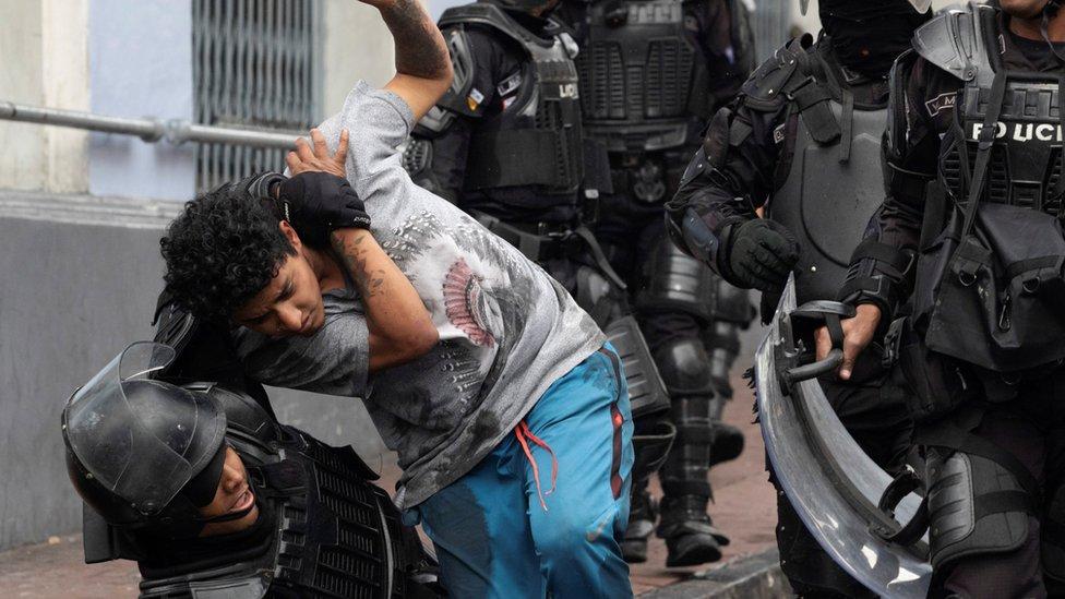 Un chico es agarrado por la policía antidisturbios.