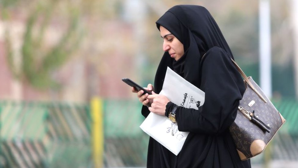 A woman in Tehran with a newspaper looking at her mobile phone