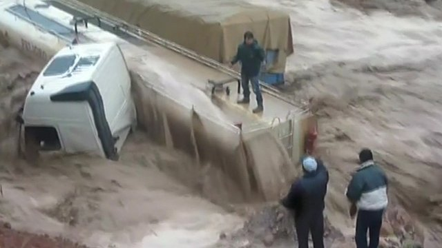 A man being saved from the top of a lorry after flood waters swept it over in Peru.
