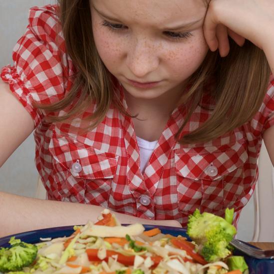 Niña con expresión triste frente a un plato de comida