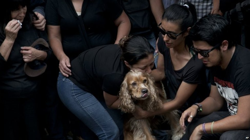 Family and friends embrace Cosmos, the dog of murdered photojournalist Ruben Espinosa during his funeral service in Mexico City on 3 August, 2015.