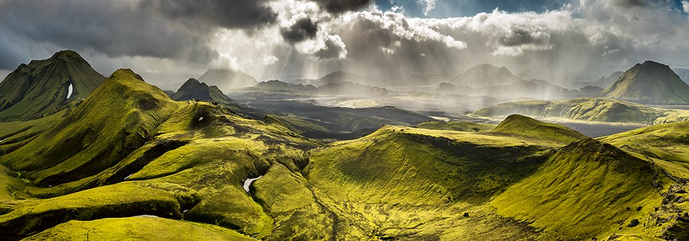 A landscape of green hills with dark clouds and sun breaking through