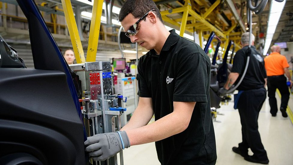 Staff members and technicians work on the Mini assembly line at the factory in Cowley
