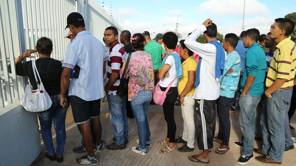 Venezuelans queue outside the federal police station in Boa Vista
