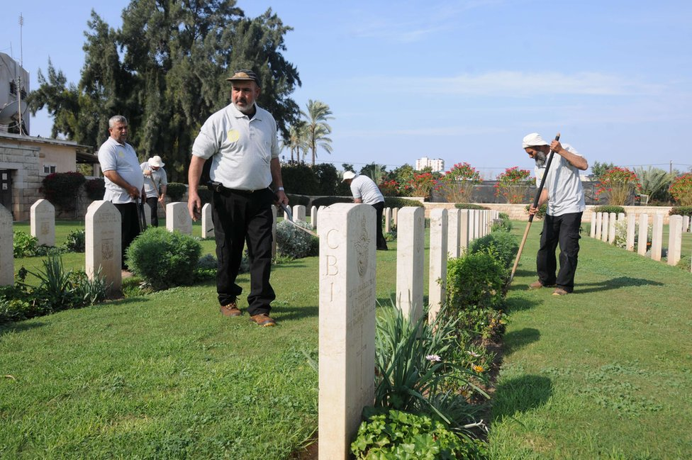 Members of the Jaradah family work to tend the laws and flowers at the cemetery in Gaza.