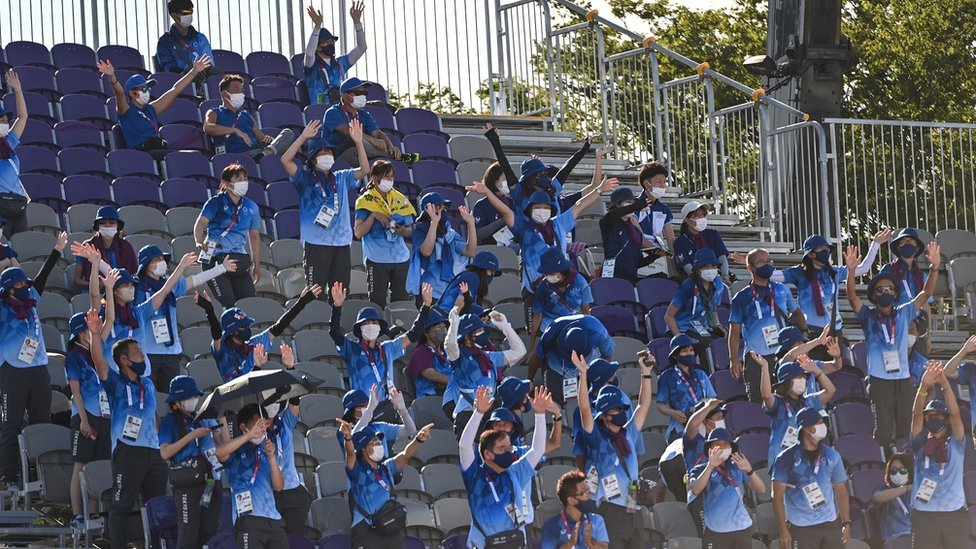 Dozens of volunteers at an Olympic event clapping.