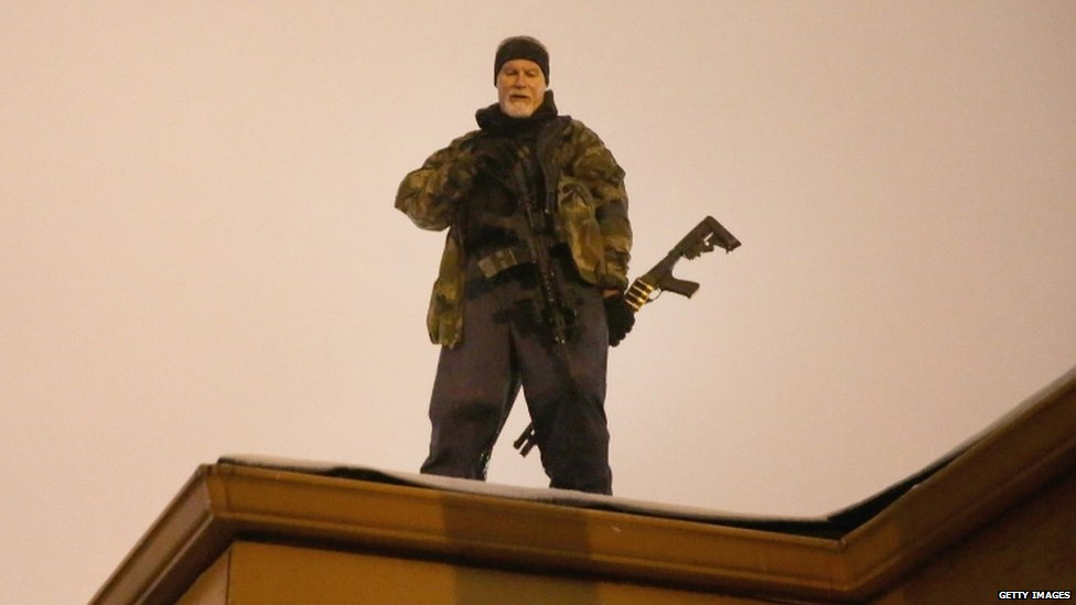 John Karriman. a volunteer from Oath Keepers, stands guard on the rooftop of a business on 26 November 2014 in Ferguson, Missouri.