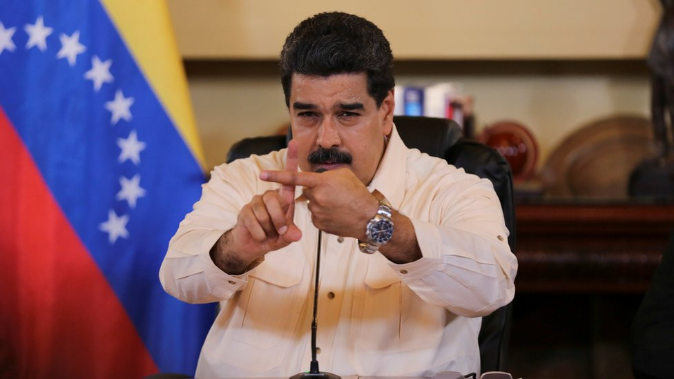 Venezuela's President Nicolas Maduro gestures toward the camera with crossed index fingers, during a meeting with ministers in Caracas