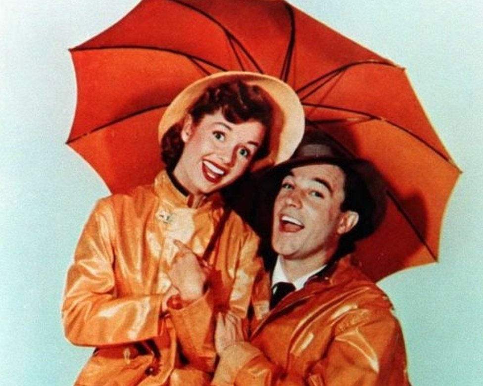 """This undated file photo shows US actor Gene Kelly, who died 02 February at the age of 83 at his home in Beverly Hills, California, with actress Debbie Reynolds from the movie """"Singin"""" in the Rain"""