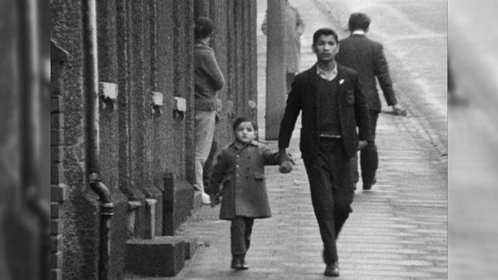 An Asian man and boy walking down a street