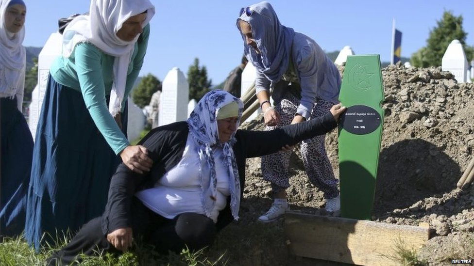An elderly woman is comforted as she cries at an open grave in Memorial Centre in Potocari, near Srebrenica.