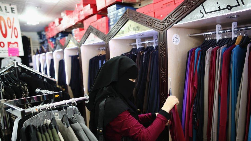 امرأة مسلمة تتفقد عباءات
