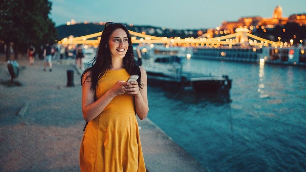 Mujer joven con un celular en sus manos. Sonríe y lleva un vestido amarillo junto al río en Budapest al atardecer